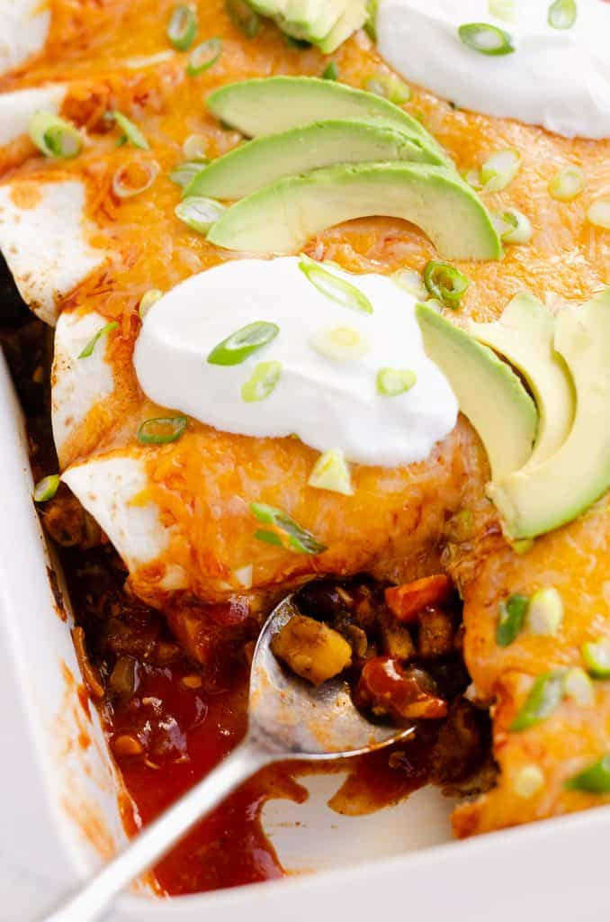 Black Bean & Squash Vegetarian Enchiladas served wtih sour cream and avocado