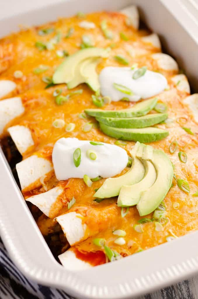 Black Bean & Squash Vegetarian Enchiladas topped with sour cream and avocado