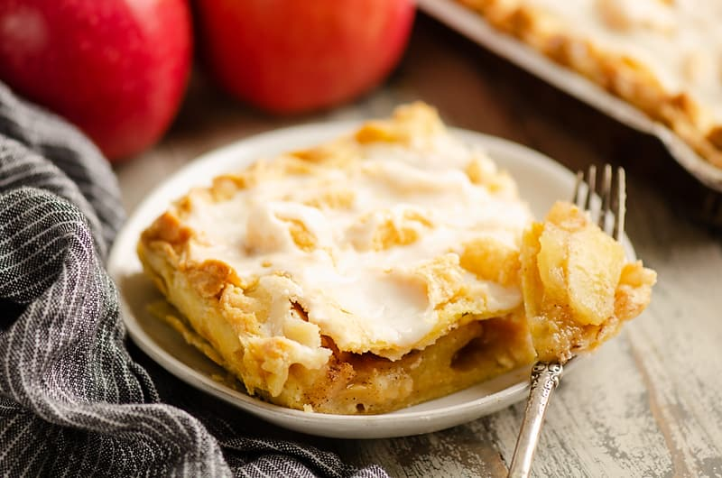 Glazed Apple Pie Bars on plate with fork full of apples