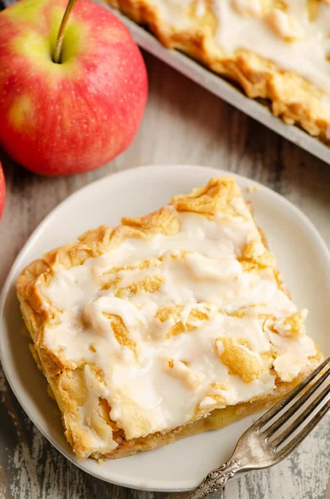Glazed Apple Pie Bars on plate with fork and apple on table