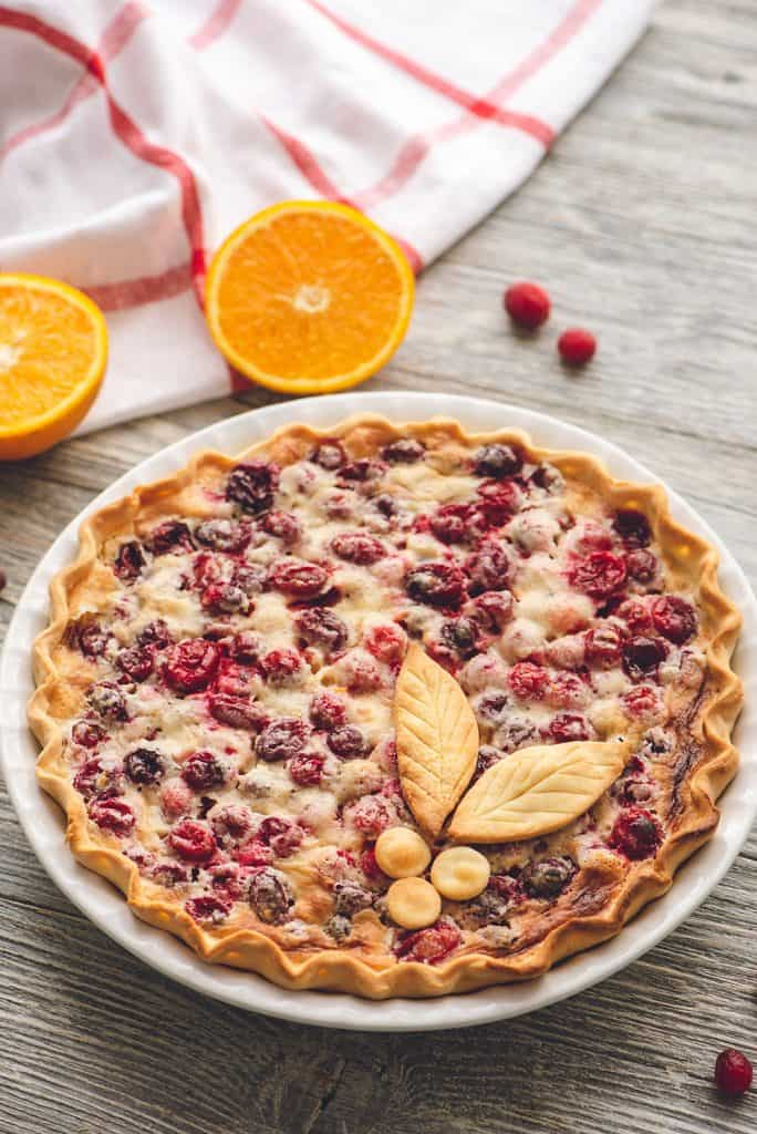 Cranberry Orange Custard Pie on table with oranges