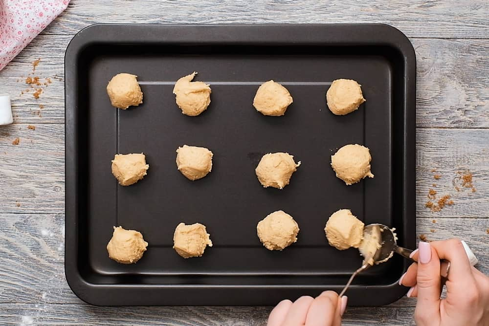 dropping cookies by spoon on cookie sheet
