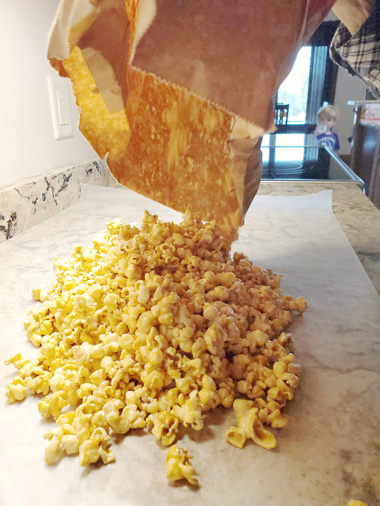 Microwave Caramel Popcorn in a brown paper bag poured on wax paper