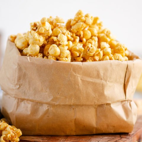 Microwave Caramel Popcorn in a brown paper bag on table with cloth napkin