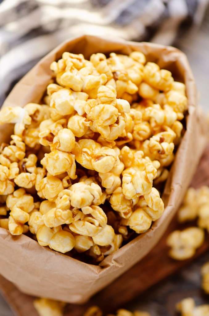 Microwave Caramel Popcorn in a brown paper bag on cutting board