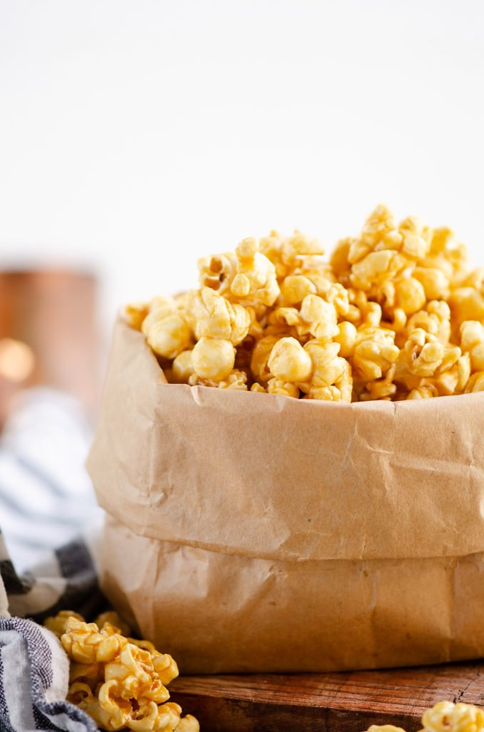 Microwave Caramel Popcorn in a brown paper bag with measuring cup
