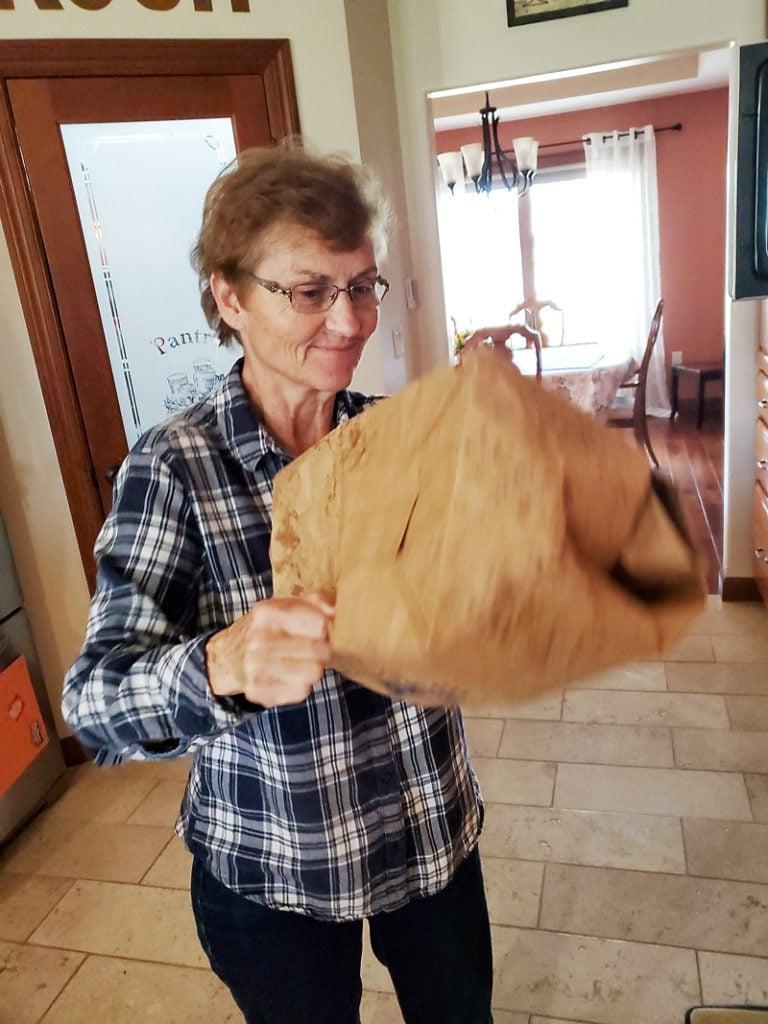 grandma shaking microwave caramel popcorn in brown paper bag