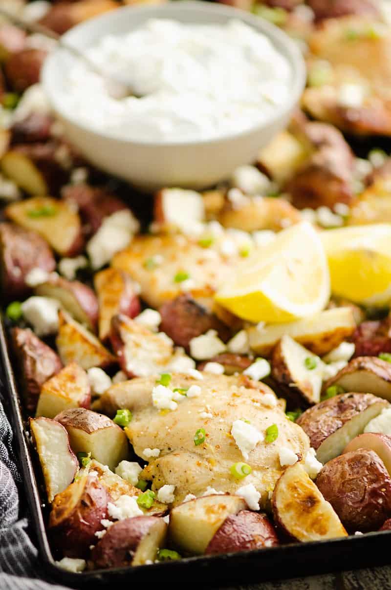 Lemon Feta Sheet Pan Chicken Thighs & Potatoes with bowl of yogurt sauce