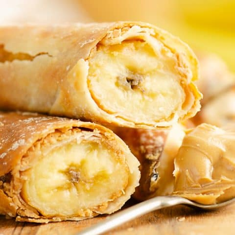 Peanut Butter Banana Egg Rolls stacked with a spoonful of peanut butter