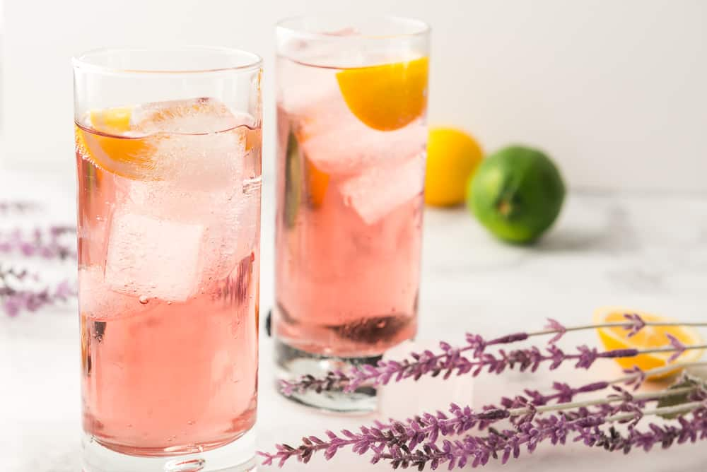 Purple Rain Cocktail on table with citrus fruits