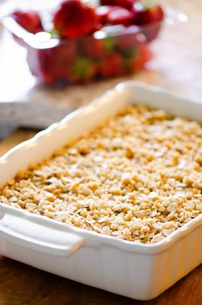 Strawberry Rhubarb Crisp Bars on kitchen counter with strawberries