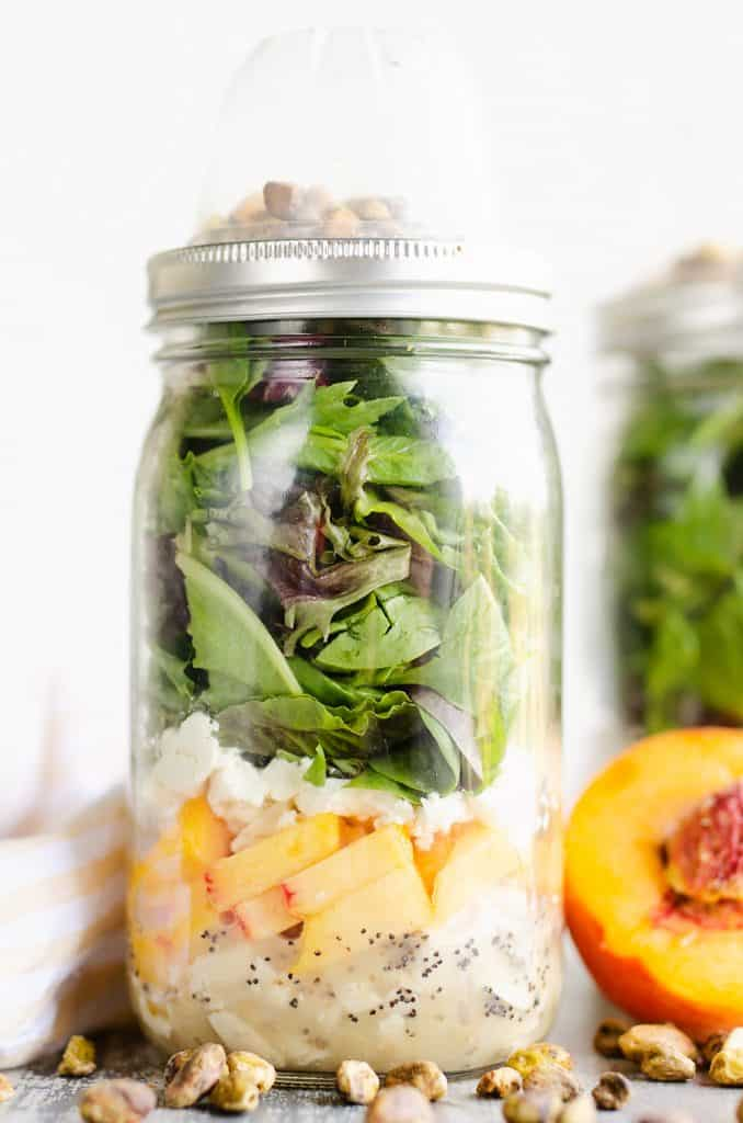 Chicken Peach Salad in a Jar on table with pistachios and fresh peaches