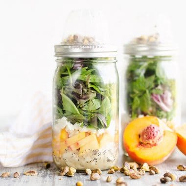 Chicken Peach Salad in a Jars on a table with pistachios and half peaches