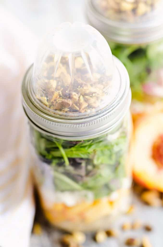 Chicken Peach Salad in a Jar topped with container of pistachios