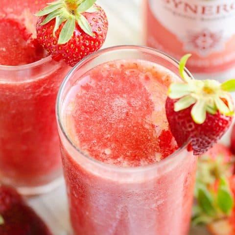 Frozen Strawberry Malibu Kombucha Cocktail on table with fresh strawberries