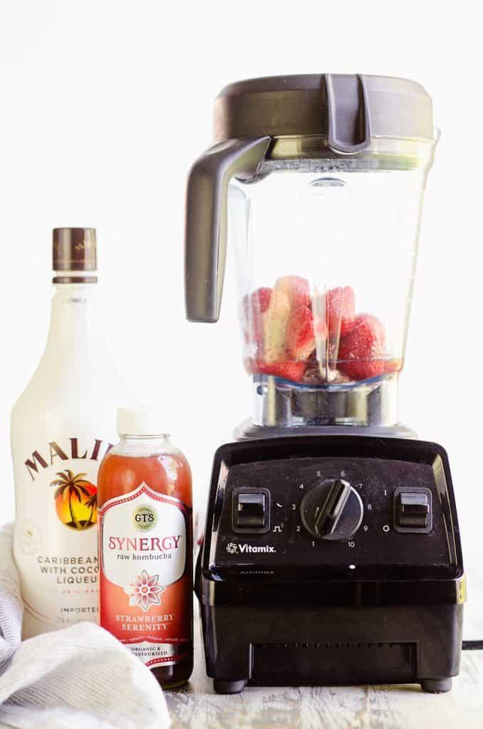 Frozen Strawberries in blender next to kombucha and Malibu rum