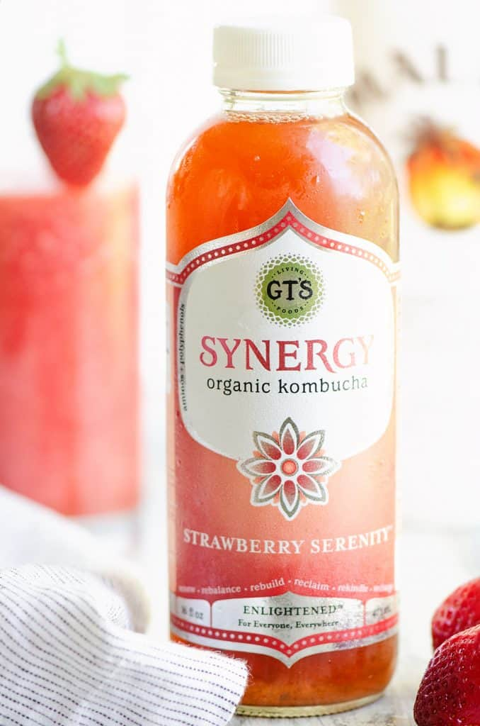 GTs Synergy Strawberry Kombucha bottle on table with cocktail and strawberries