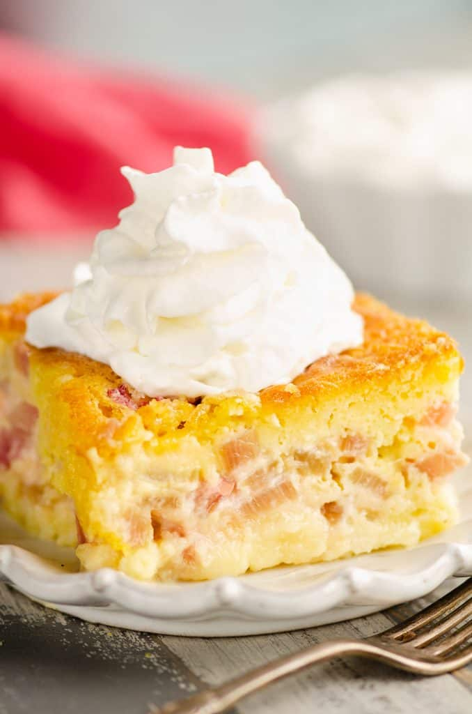 Rhubarb Custard Cake slice topped with whipped cream
