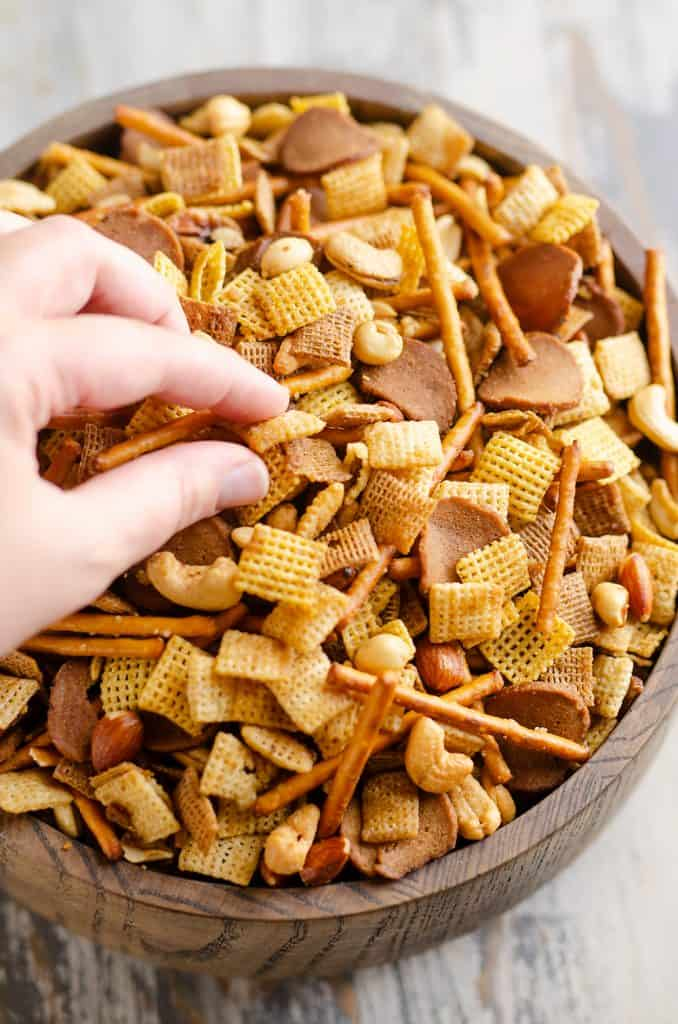 eating buttery snack mix from large wooden bowl