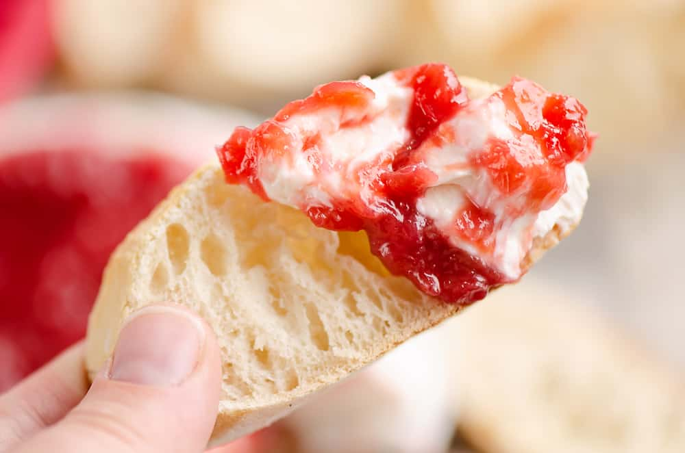 Whipped goat cheese topped with a rhubarb sauce swirled on a piece of French bread