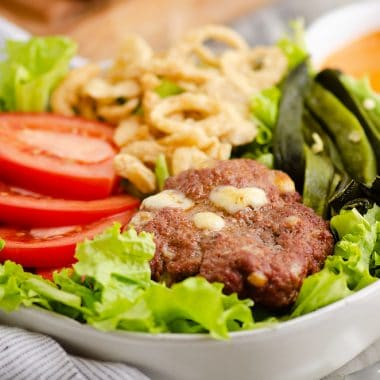 Smoked Cheese Curd Burger Salad in white bowl with side of chipotle lime southwest dressing
