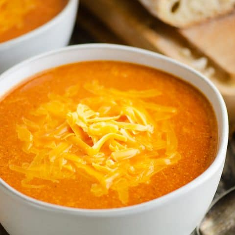 white bowl of tomato soup with bread