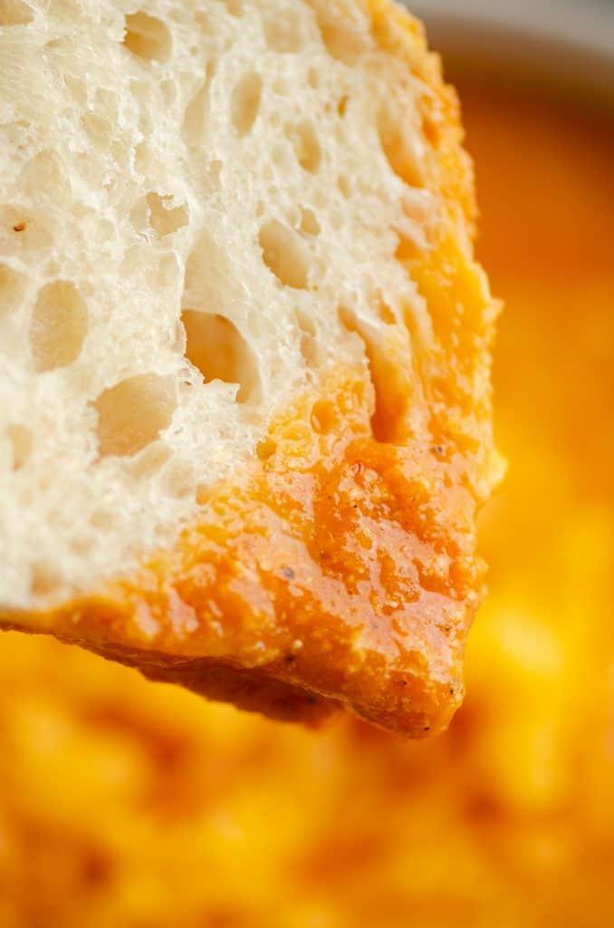 piece of sourdough bread dipped in tomato soup