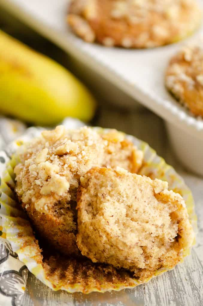 Banana Nut Muffin with Streusel Topping broke in half in yellow liner