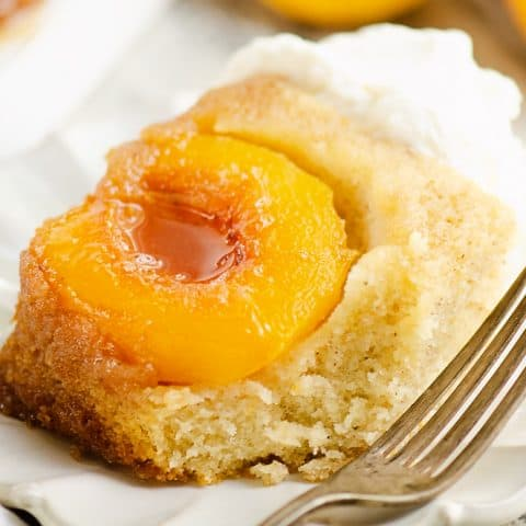 slice of Peach Upside Down Cake on white scalloped plate with fork