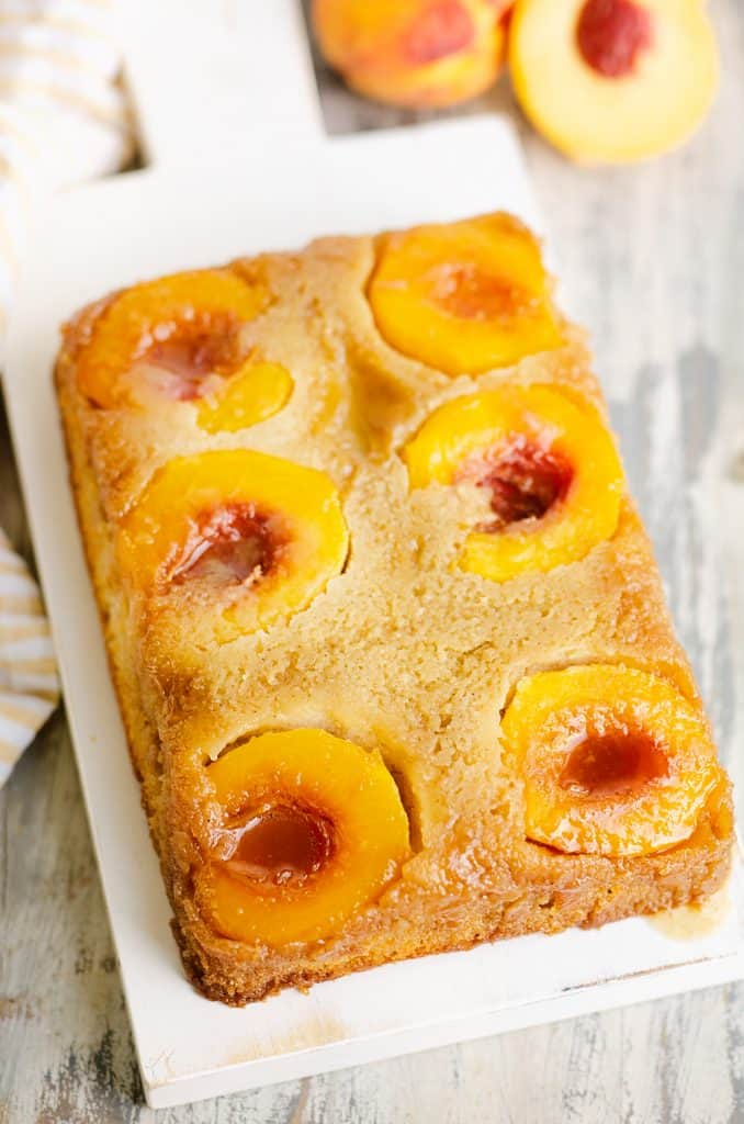 Peach Upside Down Cake on table with dish cloth