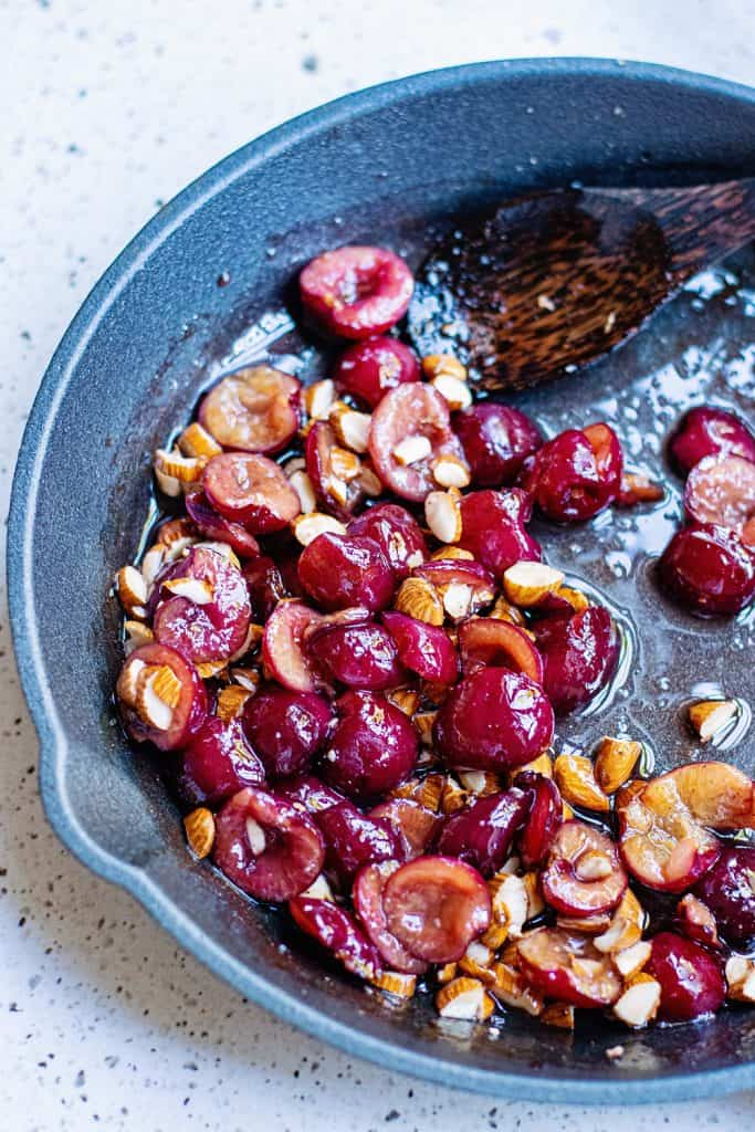 Cherries and almonds in cast iron skillet with spoon