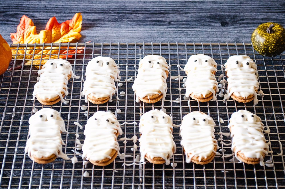 Mummy Nutter Butter Cookies drizzled with frosting on cooling rack