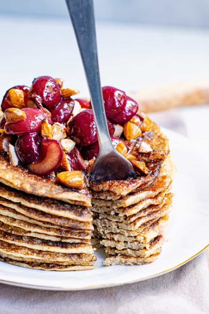 stack of Oatmeal Pancakes topped with cherry almonds and bite on fork