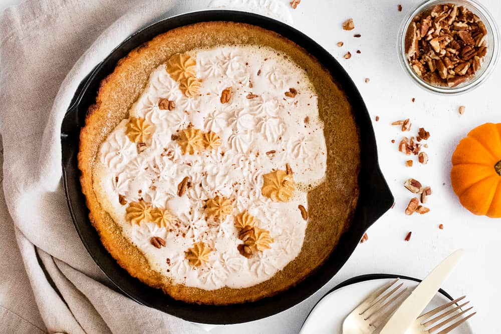 Pumpkin Spicy Dutch Baby on white table with pumpkin and pecans