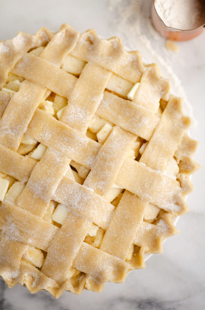 Old Fashioned Apple Pie with lattice crust on marble table