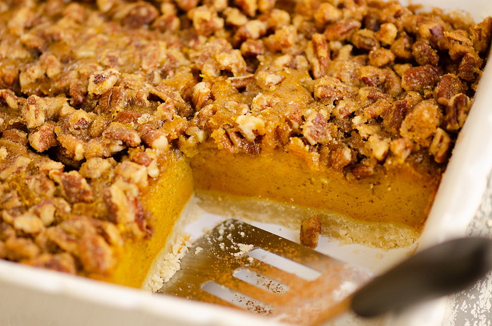 Pumpkin Pecan Custard Pie Bars in pan with spatula