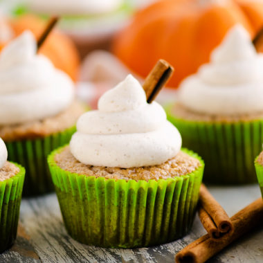 fall spiced cupcakes with buttercream swirls on table with cinnamon and pumpkins