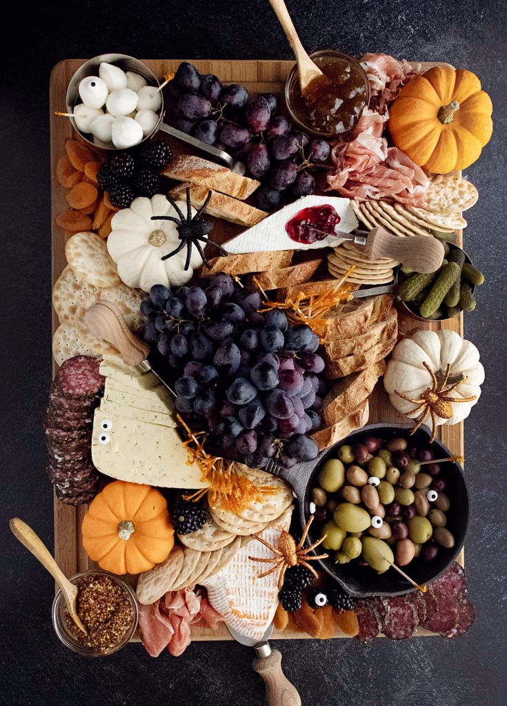 Halloween Charcuterie Board with spiders and pumpkins on cutting board