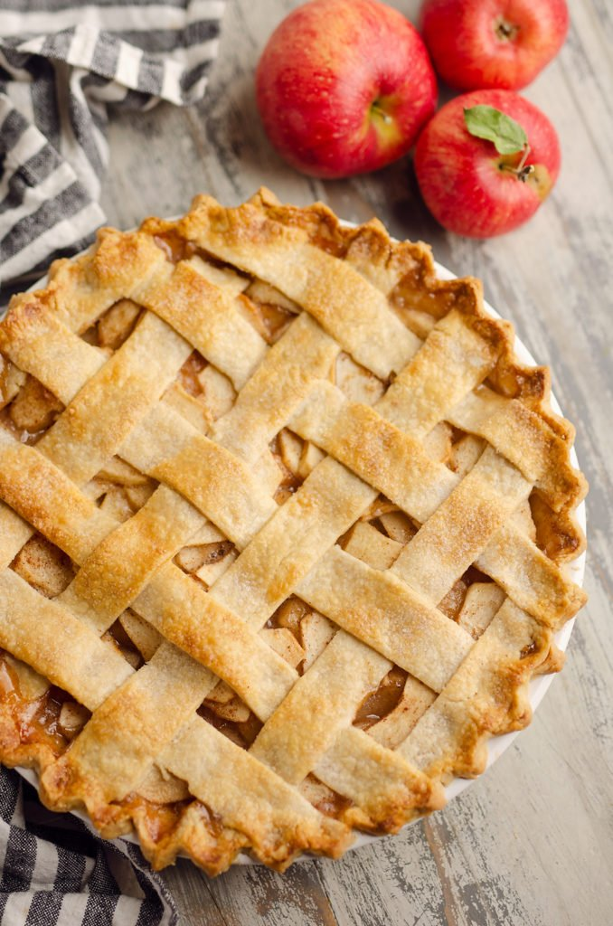 Old Fashioned Apple Pie with lattice crust on table with apples