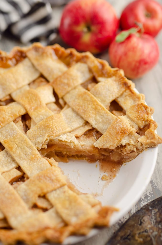 Old Fashioned Apple Pie with lattice crust in white pie plate with slice cut out