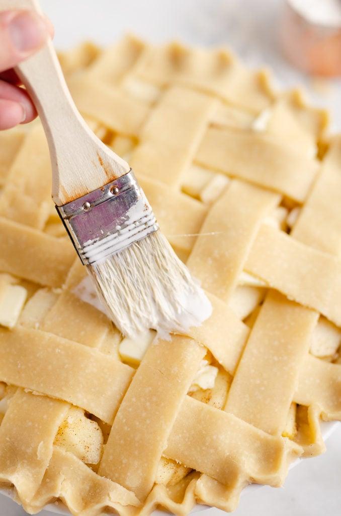 pastry brush putting cream on lattice crust of apple pie