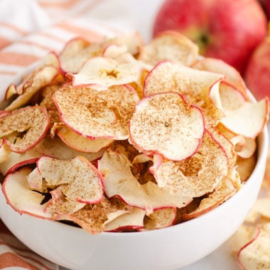 baked apple chips in bowl with apples