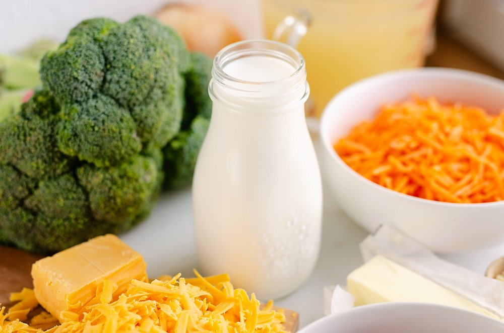 marble table with glass jar of milk, broccoli, cheese, carrots and butter