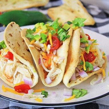 Pressure Cooker Chili Lime Chicken Tacos topped with cheese and vegetables