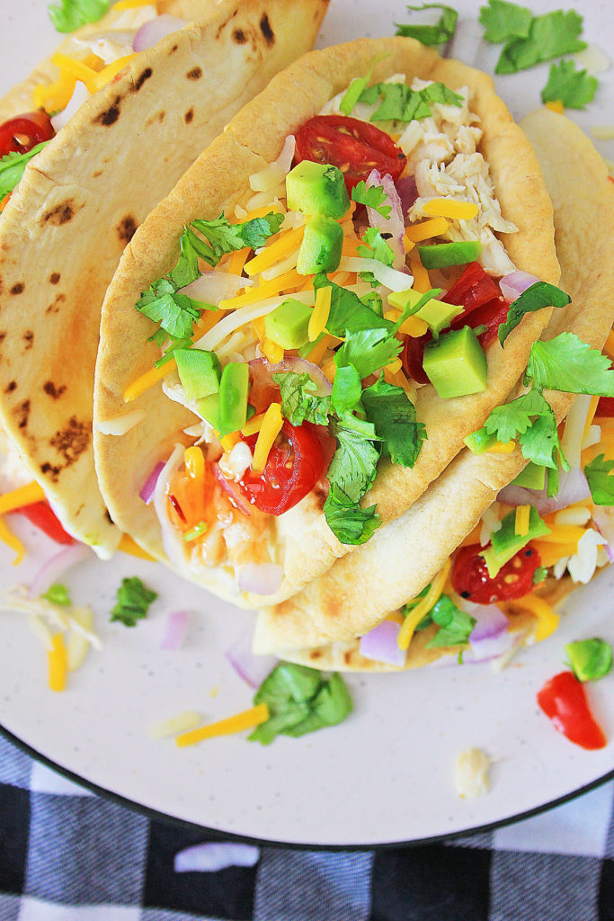 Pressure Cooker Chili Lime Chicken Tacos topped with tomatoes cheese and cilantro