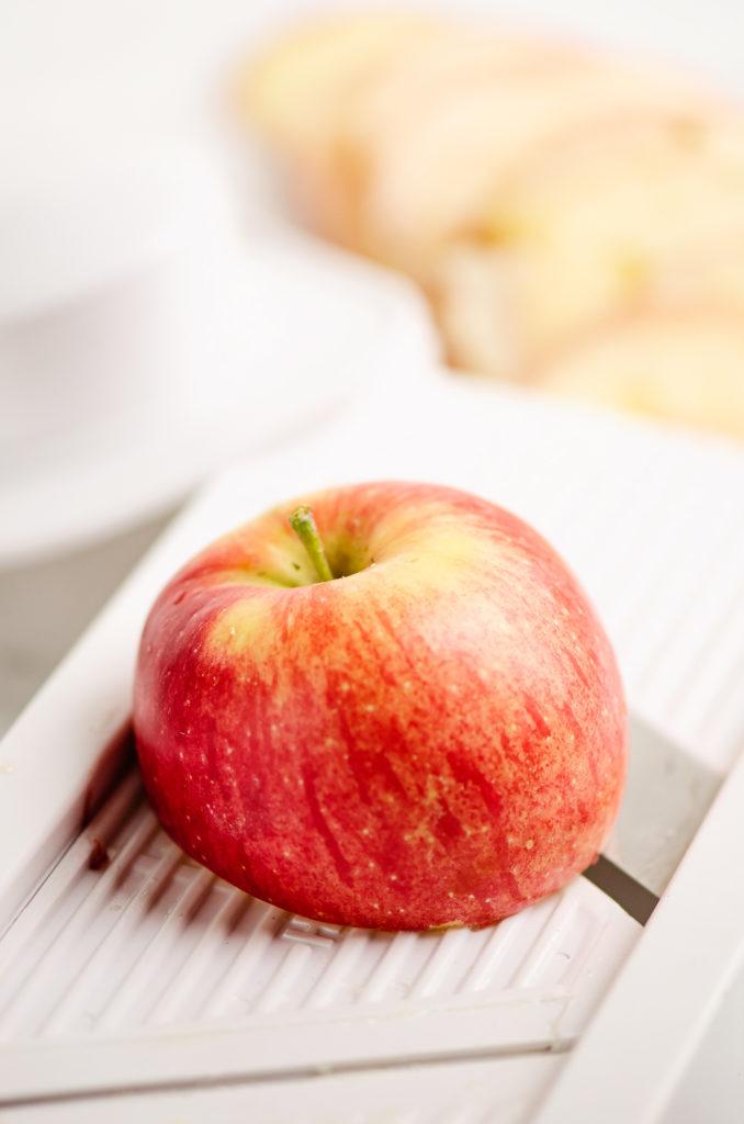 apple on mandolin being sliced