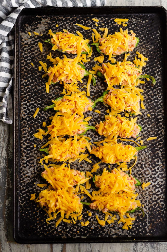 Cheesy BBQ Pork Jalapeno Poppers topped with shredded cheddar on sheet pan