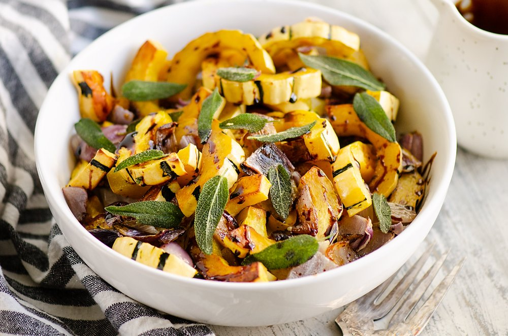 Crispy Sage Roasted Delicata Squash with balsamic glaze in white bowl