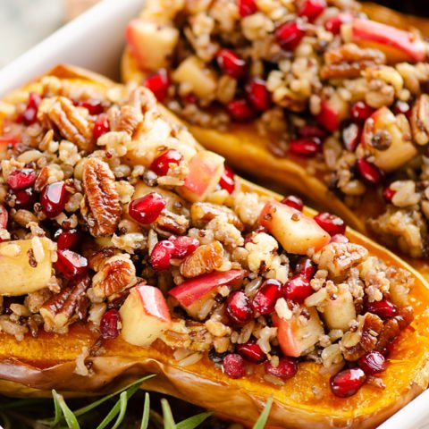 Stuffed Butternut Squash with Apples, Pomegranates & Grains in white baking pan with rosemary