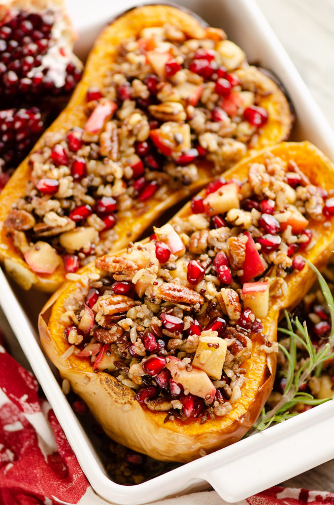 Stuffed Butternut Squash with Apples, Pomegranates & Grains in baking dish with fresh rosemary